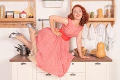 Schöner rothaariger Pinup, der glücklich Mädchen aufwirft in einem Retro- roten Kleid in der Küche allein lächelt stockfotografie