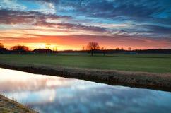 Schöner ruhiger Sonnenuntergang über Fluss im Ackerland Lizenzfreie Stockbilder