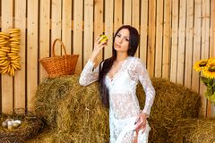 Schöner schlanker Brunette, der im weißen Kleid in der Scheune mit Hayloft, Entspannungskonzept steht stockfotografie