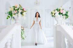 Schöner schlanker Brunette steht in einem weißen Kleid stockfoto