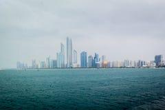 Schöner Schuss von Abu Dhabi-Stadtskylinetürmen und -strand an einem bewölkten Tag stockfoto