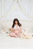 Schöner schwangerer Brunette, der auf einem Bett im Lotussitz sitzt Stockbilder