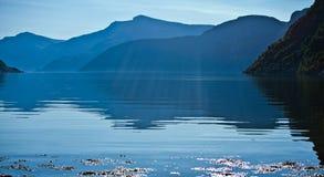 Schöner See und fallende Strahlen des Sonnenlichts in Norwegen Stockfotografie