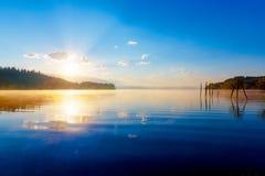 Schöner Seeblick im Morgennebel mit mystischen Bergen und Bäumen als Resten einer Mole im Gold, Purpur - blaue Töne Lizenzfreies Stockfoto