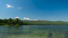 Schöner Seeblick Sommerlandschaft mit blauem Himmel, Bäumen und See, timelapse Stockbild