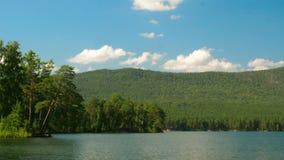 Schöner Seeblick Sommerlandschaft mit blauem Himmel, Bäumen und See, timelapse Stockfotos