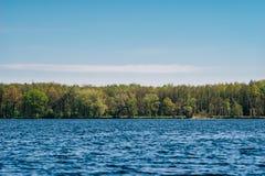 Schöner Seeufer gegen blauen Himmel bis zum sonnigem Tag des Frühlinges Lizenzfreie Stockfotografie