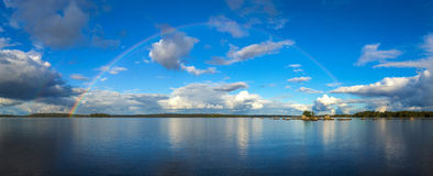 Schöner September-Regenbogen über dem See in der Panoramalandschaft Stockfotos