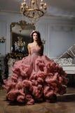 Schöner sexy Brunette im Wolkenkleid, das in einem Chicinnenraum des Studioklaviers aufwirft stockfoto