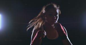 Schöner sexy Frauenboxer schlägt dynamisch direkt in die Kamera und in das Verschieben vorwärts auf einem dunklen Hintergrund mit stock video footage