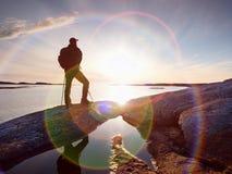 Schöner Sommersonnenuntergang an der Küste Stehender Mann mit Rucksack in Ozean gegen Sonnenuntergang stockbild