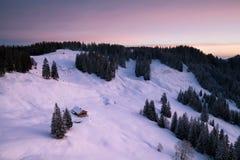 Schöner Sonnenaufgang über alter Kabine in den schneebedeckten Alpen lizenzfreie stockfotos