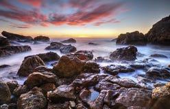 Schöner Sonnenaufgang auf felsigem Ufer Stockfoto
