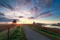 Schöner Sonnenaufgang auf niederländischem Ackerland mit Windmühle Lizenzfreies Stockfoto