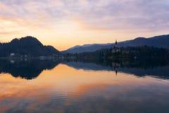 Schöner Sonnenaufgang und Kirche auf dem See geblutet in Slowenien am Frühjahr lizenzfreie stockfotos