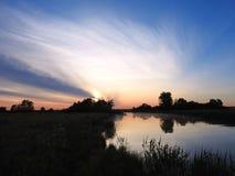 Schöner Sonnenaufgang und nette Bäume nähern sich Fluss, Litauen stockfotografie