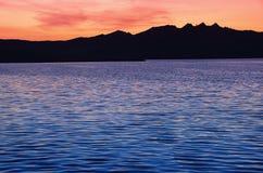 Schöner Sonnenuntergang über dem Meer und dem Berg stockbild