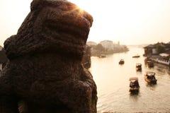 Schöner Sonnenuntergang in alter Stadt Zhujiajiao, China Traditionelle chinesische Löweskulptur, Schiffe auf Wasser, Fluss lizenzfreie stockfotografie