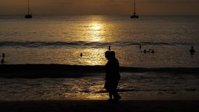 Schöner Sonnenuntergang mit Schattenbildern von Leuten genießen den Ozean stock video footage