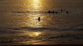 Schöner Sonnenuntergang mit Schattenbildern von Leuten genießen den Ozean stock video