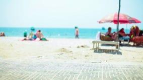 Schöner sonniger abgelegener Strand an den Feiertagen, die über Hälfte schauen, begrub Treibholz im Sand mit Weichzeichnungsleute stock footage