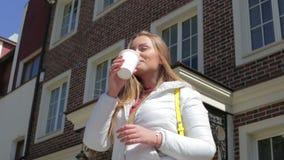 Schöner sonniger netter trinkender Kaffee der jungen Frau draußen stock video