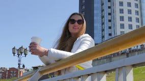Schöner sonniger netter trinkender Kaffee der jungen Frau draußen stock video footage
