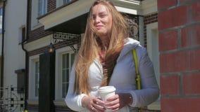 Schöner sonniger netter trinkender Kaffee der jungen Frau draußen stock footage
