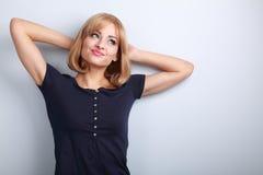 Schöner Spaß, der blonde junge Frau denkt, wenn Sie oben auf blauem b schauen Lizenzfreies Stockbild