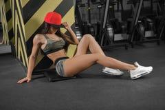 Schöner sportlicher Brunette in einer Kappe sitzt auf dem Boden in der Turnhalle nach einem Training lizenzfreies stockbild