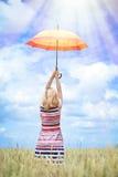 Schöner steigender bunter Regenschirm der jungen Frau an Lizenzfreie Stockfotografie