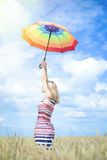 Schöner steigender Regenbogenregenschirm junger Dame an Lizenzfreie Stockfotografie