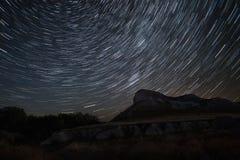 Schöner Stern schleppt Zeitversehen über den Hügeln Polarer Nordstern in der Mitte der Rotation Lizenzfreie Stockfotografie