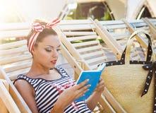 Schöner Stift herauf das Mädchen, welches das Buch nahe dem Swimmingpool liest Stockfoto