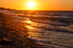 Schöner Strand auf griechischer Insel im Sommer, unter warmem Sonnenunterganglicht Stockfotos