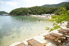 Schöner Strand mit sunbeds und Palmen Lizenzfreie Stockfotos