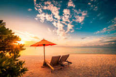 Schöner Strandsonnenuntergang mit Sonnenbetten und entspannender Stimmung lizenzfreie stockfotos