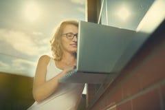 Schöner Student, der mit Laptop nahe bei der Backsteinmauer arbeitet Stockfotografie