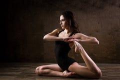 Schöner Tänzer des jungen Mädchens mit dem langen flüssigen Haar in der schwarzen Kleidung, ein gymnastischer Badeanzug, in einer Lizenzfreies Stockbild