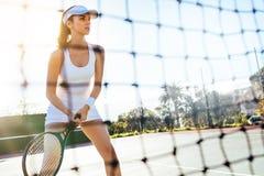 Schöner Tennisspieler mit Schläger auf Gericht Stockfotografie