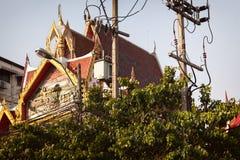 Schöner thailändischer Tempel undeutlich gemacht durch Bäume und elektrische Drähte Stockfotografie
