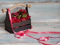 Schöner Topf Blumen eingewickelt im roten Papier, Geschenk in einem hölzernen Korb Lizenzfreie Stockfotografie