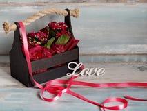 Schöner Topf Blumen eingewickelt im roten Papier, Geschenk in einem hölzernen Korb, mit Liebe Lizenzfreie Stockfotografie