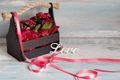 Schöner Topf Blumen eingewickelt im roten Papier, Geschenk in einem hölzernen Korb, mit Liebe Lizenzfreies Stockfoto