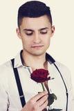 Schöner träumerischer Kerl mit einer Rose stockbilder