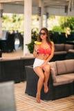 Schöner tragender Badeanzug der jungen Frau, der ein buntes Cocktail sitzt auf einer Kabine der Strandclubbar trinkt betäuben stockfotografie