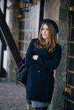 Schöner tragender Hut der jungen Frau und dunkelblauer Mantel, die auf eine Stadtstraße geht lizenzfreie stockfotografie