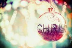 Schöner transparenter Weihnachtsball mit dem Schnee, hängend an Feiertagsbeleuchtung bokeh Hintergrund Lizenzfreie Stockfotografie