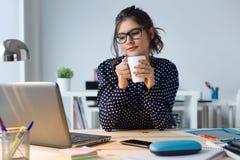 Schöner trinkender Kaffee der jungen Frau in ihrem Büro Lizenzfreie Stockfotografie