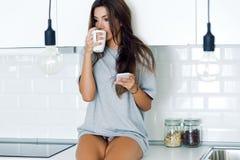 Schöner trinkender Kaffee der jungen Frau und Anwendung ihres Handys stockfotos